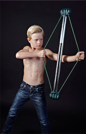 Boy using chest expander Stock Photo - Premium Royalty-Free, Code: 614-06311723