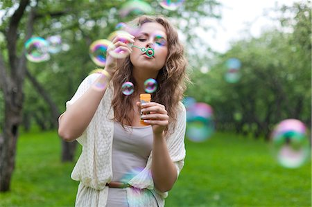 Young woman blowing bubbles Stock Photo - Premium Royalty-Free, Code: 614-06311840