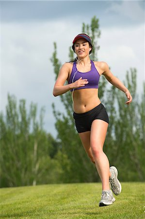 Young woman running in park Stock Photo - Premium Royalty-Free, Code: 614-06311866