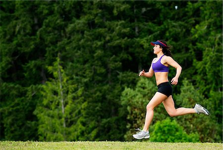 Young woman running in park Stock Photo - Premium Royalty-Free, Code: 614-06311863