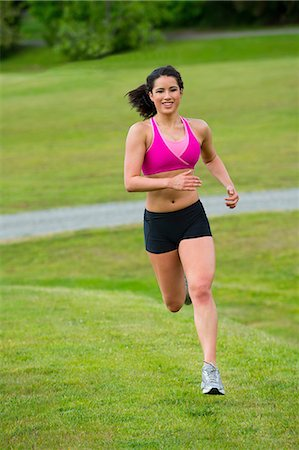 Young woman running in park Stock Photo - Premium Royalty-Free, Code: 614-06311872
