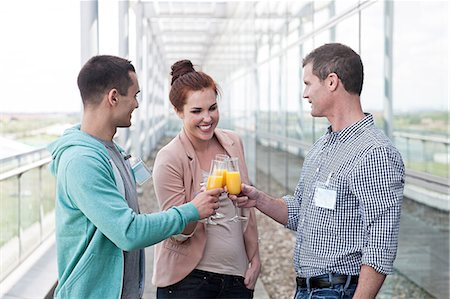 Colleagues toasting with orange juice Stock Photo - Premium Royalty-Free, Code: 614-06311930