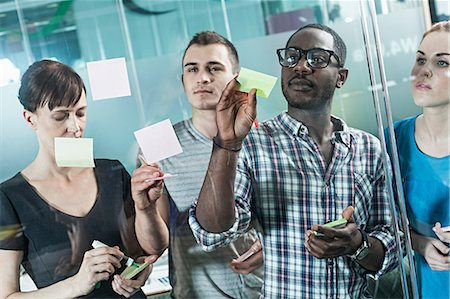 self adhesive note - Colleagues writing on adhesive notes and sticking them to window Stock Photo - Premium Royalty-Free, Code: 614-06311944