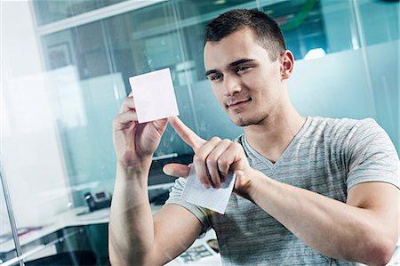 stick - Man sticking adhesive note to window Stock Photo - Premium Royalty-Free, Code: 614-06311954