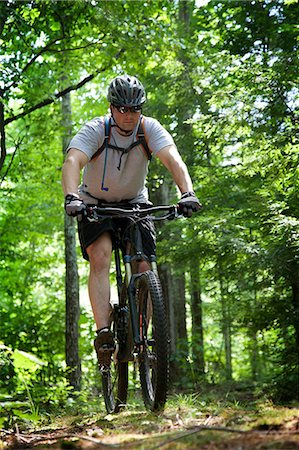 Man mountain biking in forest Stock Photo - Premium Royalty-Free, Code: 614-06311966