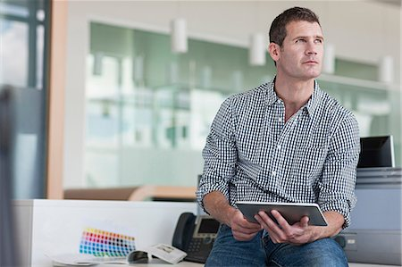 Man with digital tablet looking away Stock Photo - Premium Royalty-Free, Code: 614-06311963