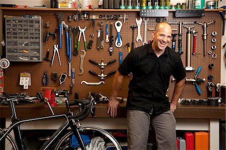 Man laughing in bicycle repair shop Stock Photo - Premium Royalty-Free, Code: 614-06311986