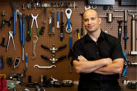 Man in front of wall of tools in workshop Stock Photo - Premium Royalty-Free, Code: 614-06311987