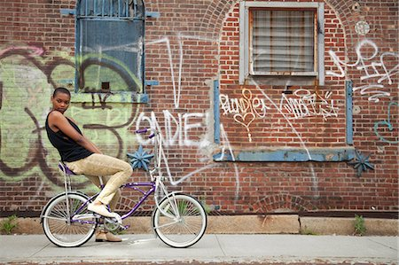 Portrait of a young woman on bicycle by wall covered in graffiti Stock Photo - Premium Royalty-Free, Code: 614-06311992