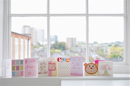 Greetings cards for new baby girl on windowsill Stock Photo - Premium Royalty-Free, Code: 614-06312009