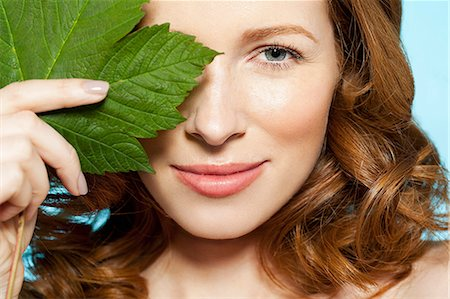 Woman covering eye with green leaf Stock Photo - Premium Royalty-Free, Code: 614-06312047