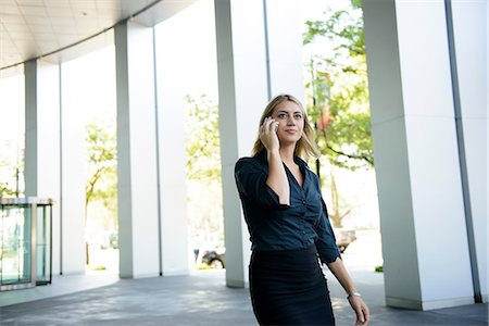 Businesswoman in front of office on cellphone Stock Photo - Premium Royalty-Free, Code: 614-06336164