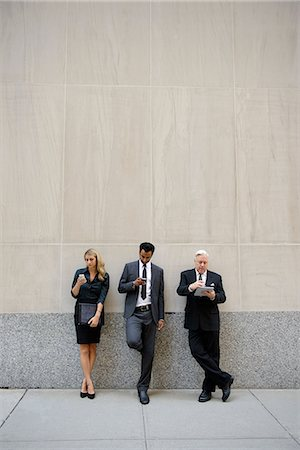 Three businesspeople leaning on a wall, looking at phones and digital tablets Stock Photo - Premium Royalty-Free, Code: 614-06336173