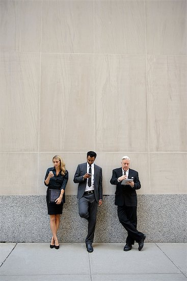 Three businesspeople leaning on a wall, looking at phones and digital tablets Stock Photo - Premium Royalty-Free, Image code: 614-06336173