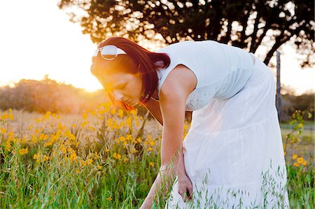 Woman picking flowers in field in sunlight Stock Photo - Premium Royalty-Free, Code: 614-06336186