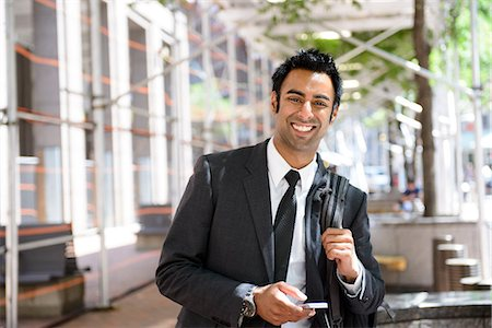 Businessman with cellphone and backpack Stock Photo - Premium Royalty-Free, Code: 614-06336181