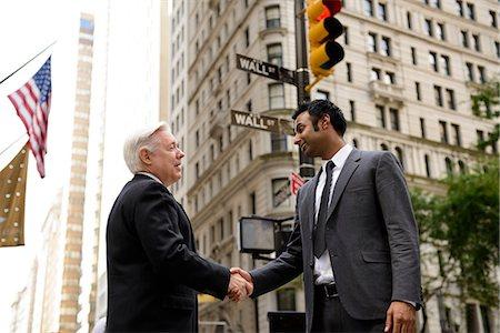 Businessmen shaking hands on Wall Street, New York City Stock Photo - Premium Royalty-Free, Code: 614-06336182