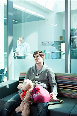 Man in hospital waiting room with bouquet and teddy bear Stock Photo - Premium Royalty-Free, Code: 614-06336267