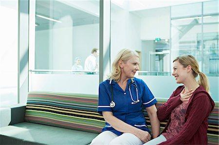Nurse talking to woman in hospital waiting room Stock Photo - Premium Royalty-Free, Code: 614-06336270