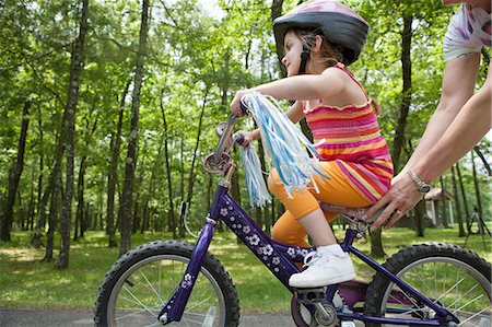 Mother helping daughter to ride bicycle Stock Photo - Premium Royalty-Free, Code: 614-06336286