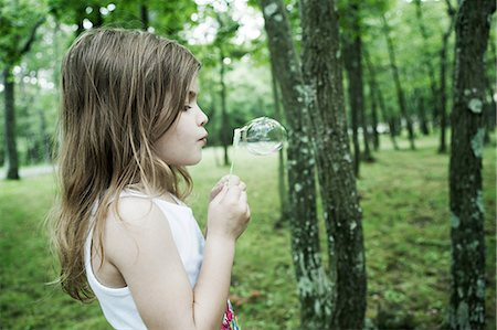 Girl blowing bubbles in forest Stock Photo - Premium Royalty-Free, Code: 614-06336304