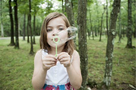 Girl blowing bubbles in forest Stock Photo - Premium Royalty-Free, Code: 614-06336305