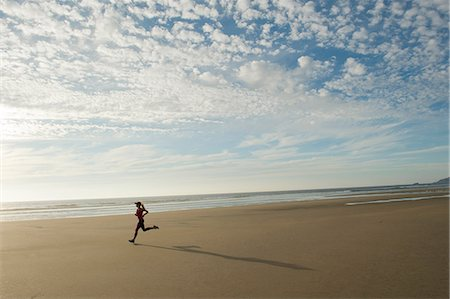 fit people - Young woman running on beach Stock Photo - Premium Royalty-Free, Code: 614-06336438