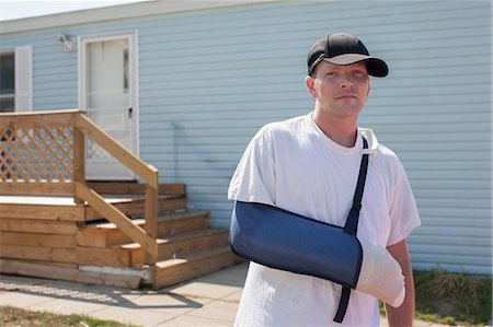 Man outside house with arm in sling Stock Photo - Premium Royalty-Free, Code: 614-06336456