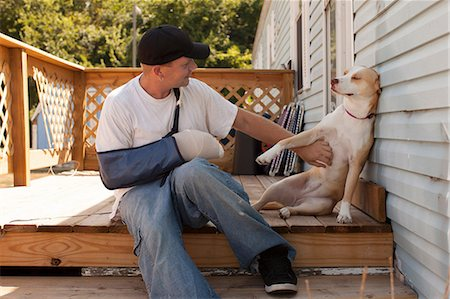 Man outside house with arm in sling and dog Stock Photo - Premium Royalty-Free, Code: 614-06336457