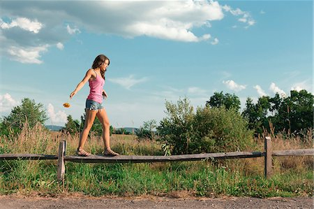 Teenage girl balancing on wooden fence Stock Photo - Premium Royalty-Free, Code: 614-06402516