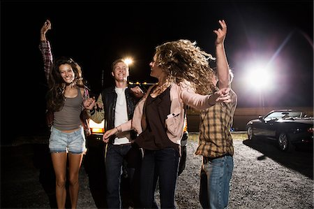 person walking on parking lot - Four friends in parking lot at night Stock Photo - Premium Royalty-Free, Code: 614-06402554