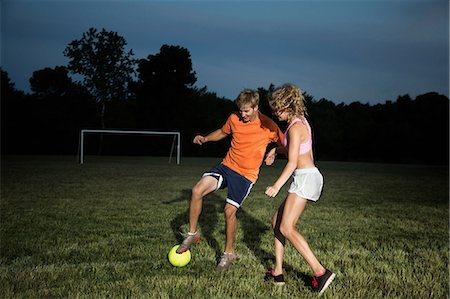 female playing soccer - Friends playing soccer at night Stock Photo - Premium Royalty-Free, Code: 614-06402565