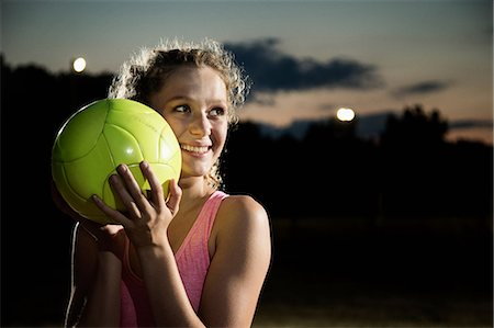 portrait looking away - Girl holding soccer ball at night Stock Photo - Premium Royalty-Free, Code: 614-06402571