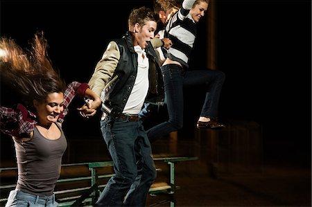 Three friends jumping over bleachers at night Stock Photo - Premium Royalty-Free, Code: 614-06402598