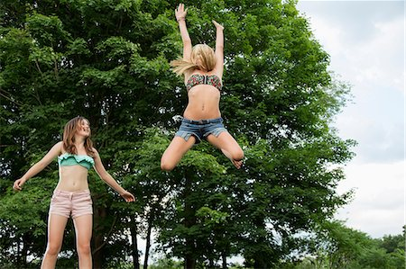 preteen girls stretching - Two girls on trampoline Stock Photo - Premium Royalty-Free, Code: 614-06402641