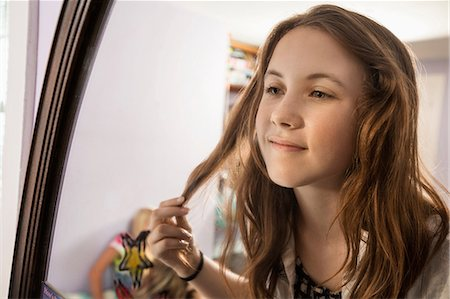 preteen touch - Girl looking in mirror, touching hair Stock Photo - Premium Royalty-Free, Code: 614-06402663