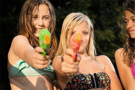Girls aiming water pistols at camera Stock Photo - Premium Royalty-Free, Code: 614-06402675