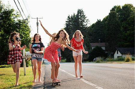Girl on skateboard with friends Stock Photo - Premium Royalty-Free, Code: 614-06402670