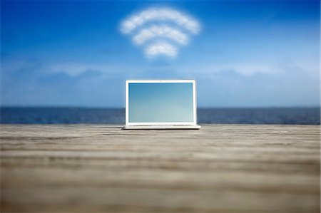 symbol - Laptop with wifi symbol at the coast Stock Photo - Premium Royalty-Free, Code: 614-06402726