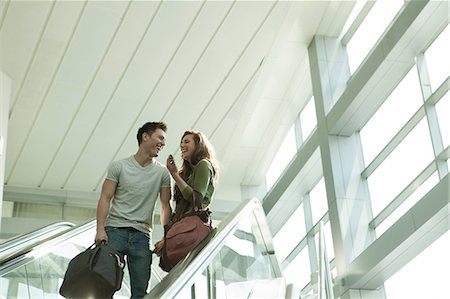 people on mall - Young couple travelling on escalator Stock Photo - Premium Royalty-Free, Code: 614-06402755