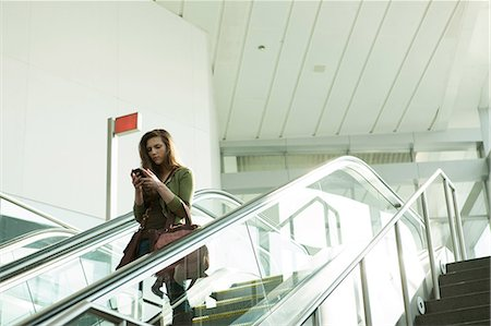 people on mall - Young woman on escalator using smartphone Stock Photo - Premium Royalty-Free, Code: 614-06402753