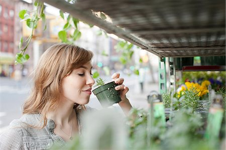 selecting - Young woman smelling a plant Stock Photo - Premium Royalty-Free, Code: 614-06402773