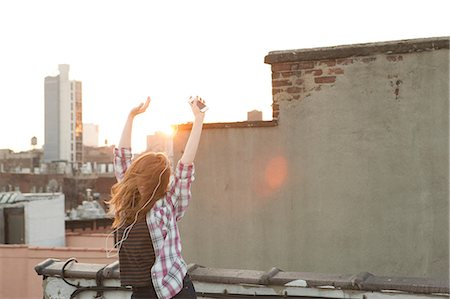 Young woman listening to music with arms raised on city rooftop Stock Photo - Premium Royalty-Free, Code: 614-06402780