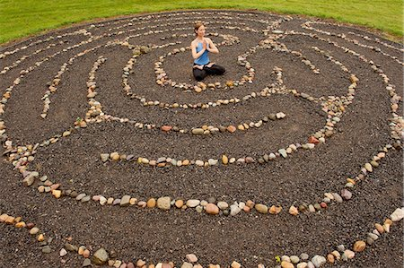 Woman meditating in stone labyrinth Stock Photo - Premium Royalty-Free, Code: 614-06402794