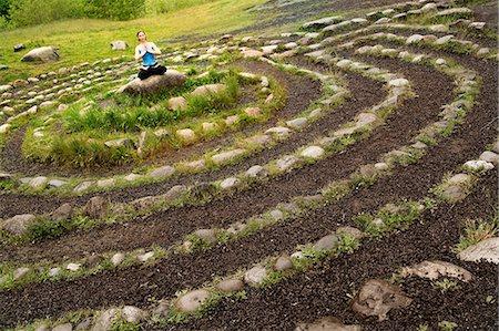 Woman meditating in stone labyrinth Stock Photo - Premium Royalty-Free, Code: 614-06402795