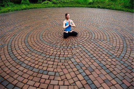 Woman meditating in paving stone circles Stock Photo - Premium Royalty-Free, Code: 614-06402798