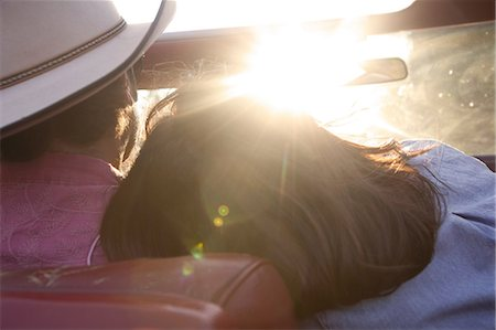 road trip - Woman resting head on boyfriend's shoulder as he drives in sunlight Stock Photo - Premium Royalty-Free, Code: 614-06402855
