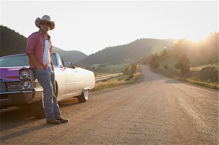Man in cowboy hat, leaning against convertible car Stock Photo - Premium Royalty-Free, Code: 614-06402856