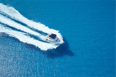 Motor yacht ploughing across blue sea Stock Photo - Premium Royalty-Free, Code: 614-06402868