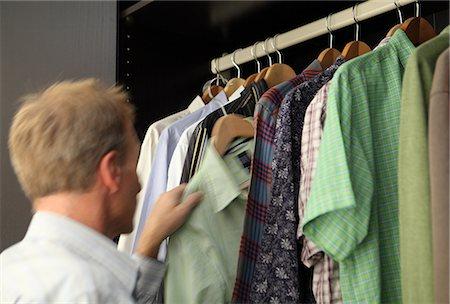 Man taking shirt from wardrobe Stock Photo - Premium Royalty-Free, Code: 614-06402955